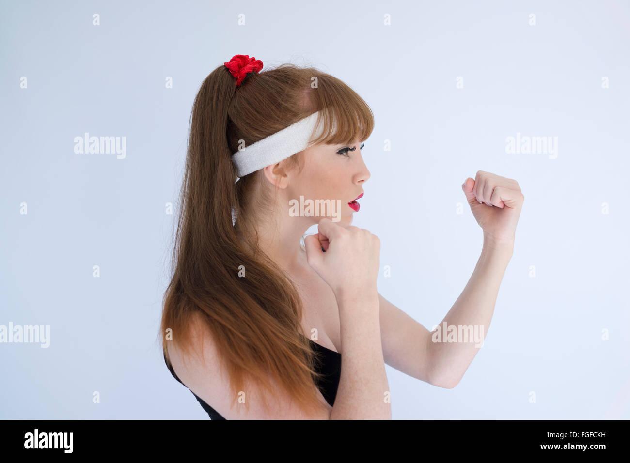 Mujer con el cabello marrón largo vistiendo una vincha de cabeza con sus puños clenched preparándose para participar Foto de stock