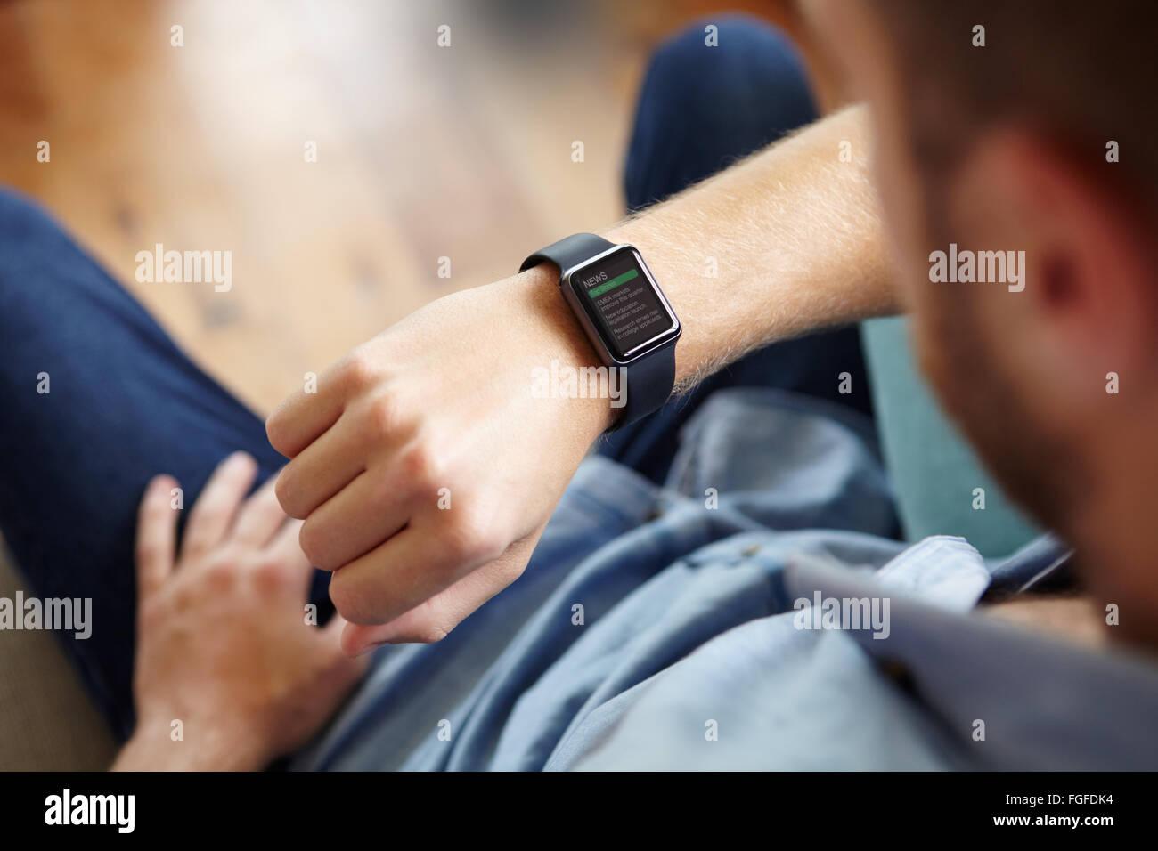 Hombre mirando las noticias sobre software de aplicación Smart Watch Imagen De Stock