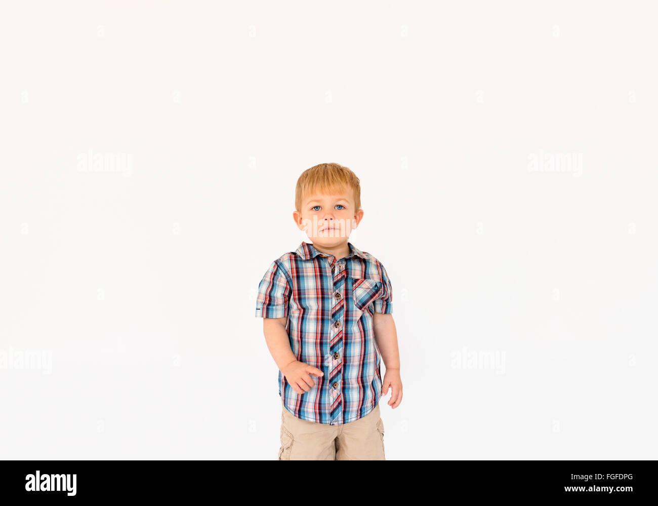 Chico con el pelo rubio de pie contra un fondo blanco apuntando con su dedo Foto de stock