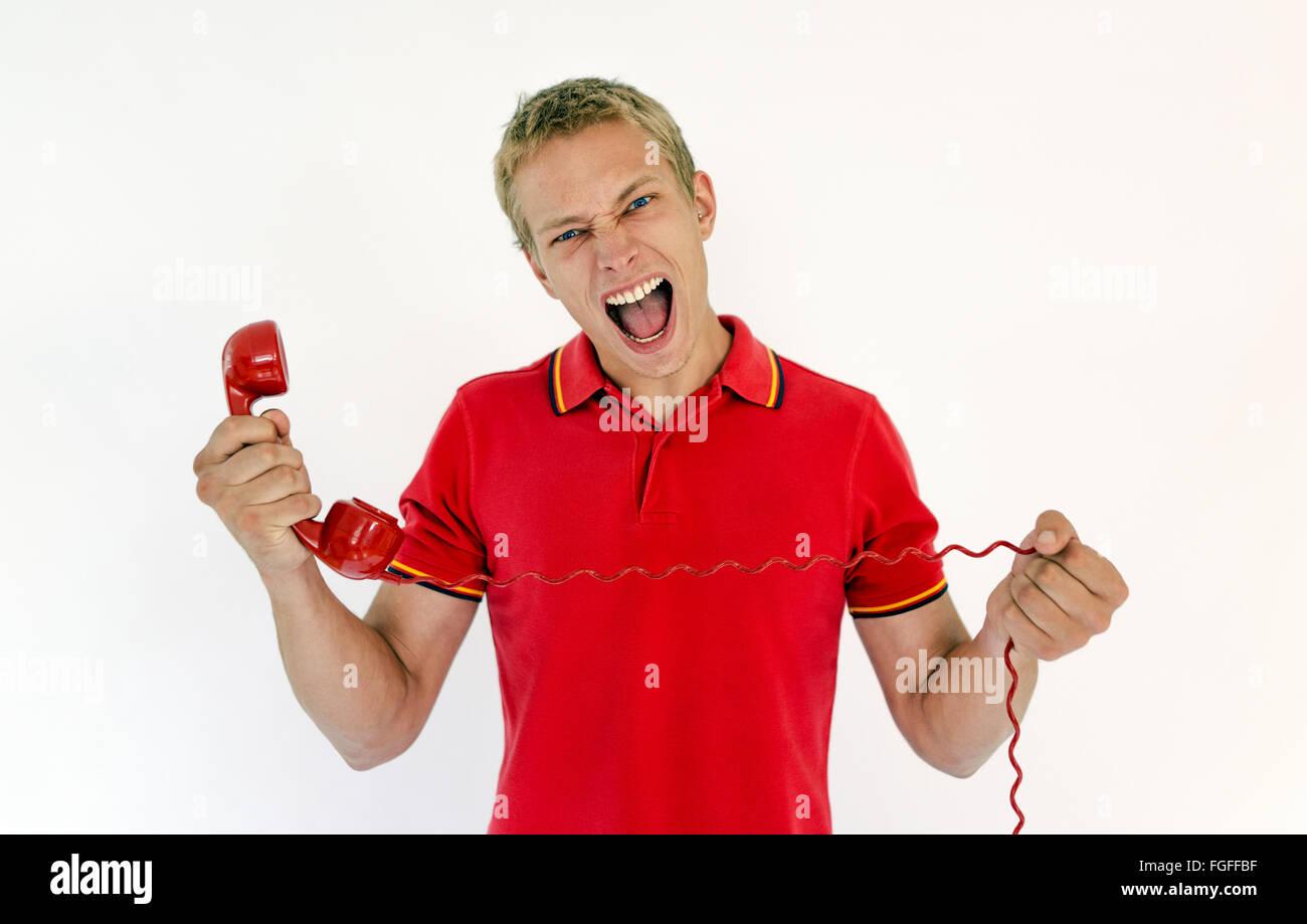 Hombre sujetando un teléfono rojo retro gritando Foto de stock