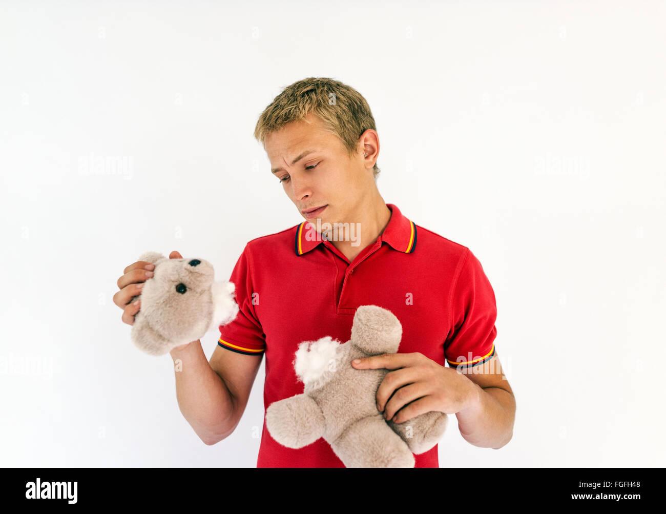 Hombre sujetando la cabeza y el cuerpo de un lindo oso de peluche juguetes buscando triste Foto de stock