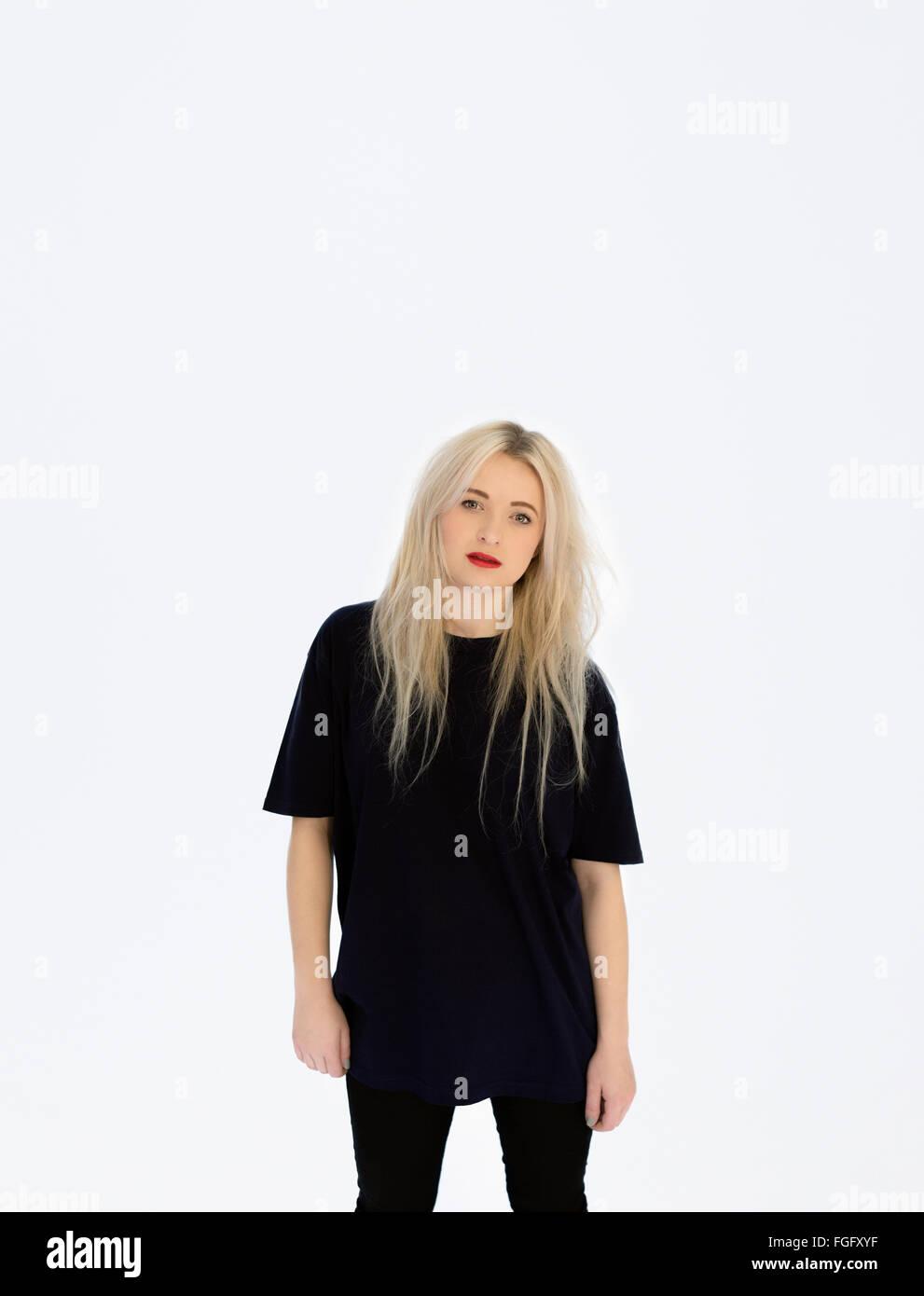 Retrato de una mujer vistiendo negro de pie contra un fondo completamente blanco Foto de stock