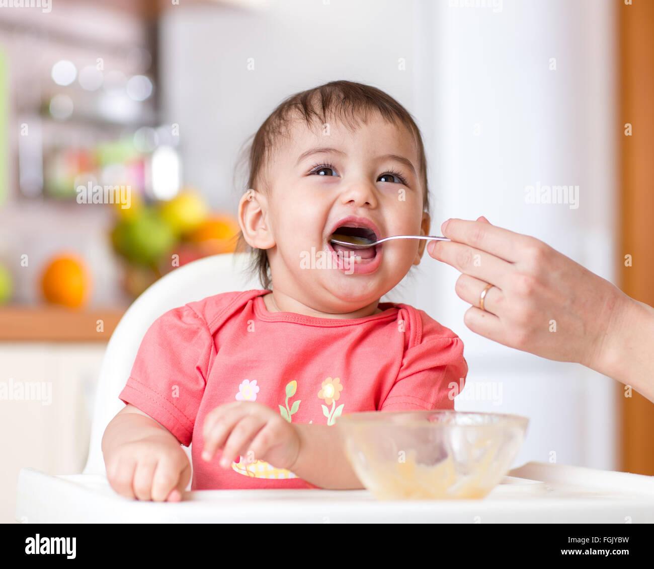 Bebé sonriente comiendo la comida en la cocina Imagen De Stock