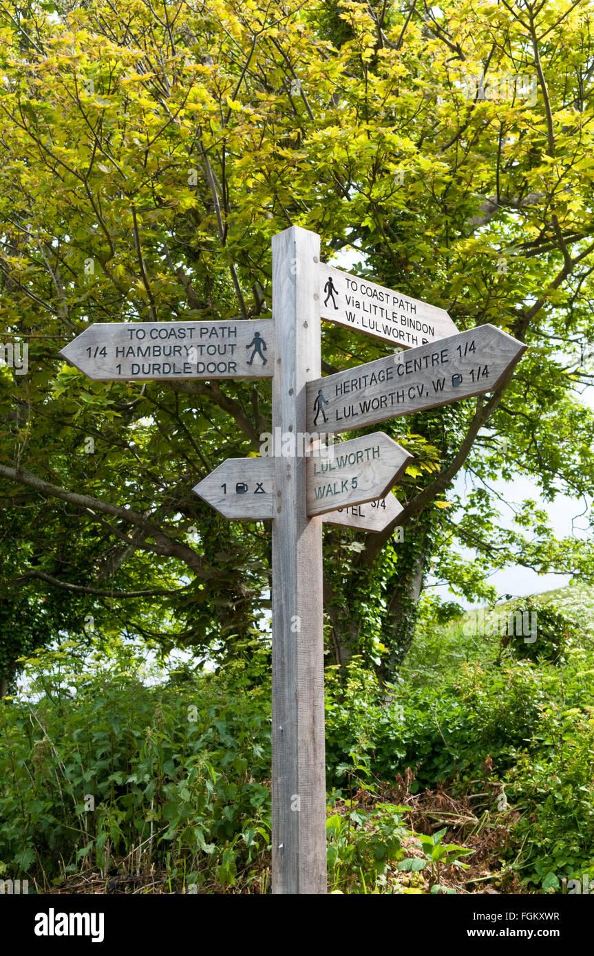 Cartel de madera para mostrar las direcciones de senderos alrededor de West Lulworth, Dorset, Inglaterra Foto de stock