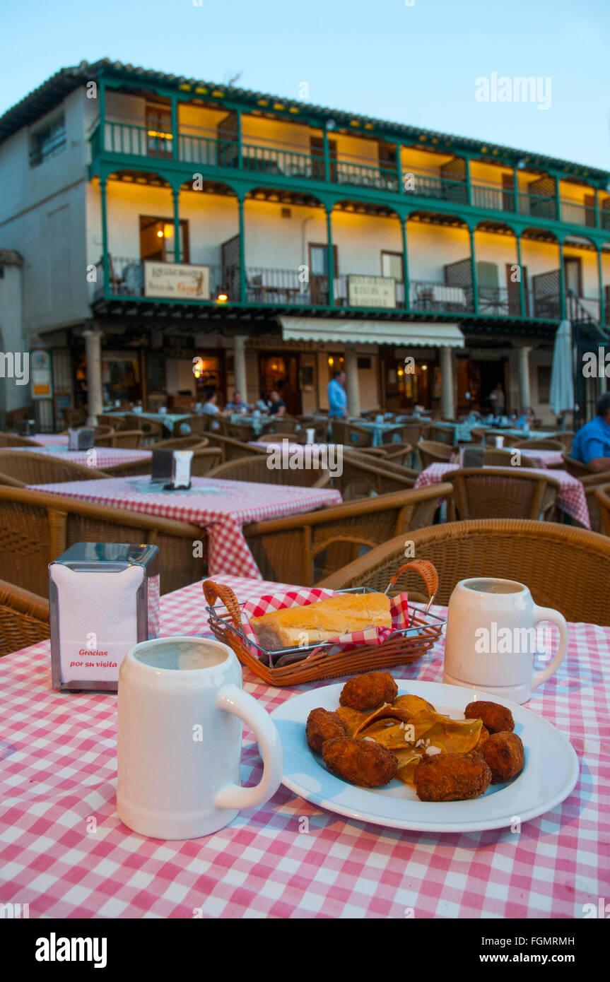 Tapa española: croquetas sirviendo y dos jarras de cerveza en una terraza. Plaza principal, Chinchón, Imagen De Stock