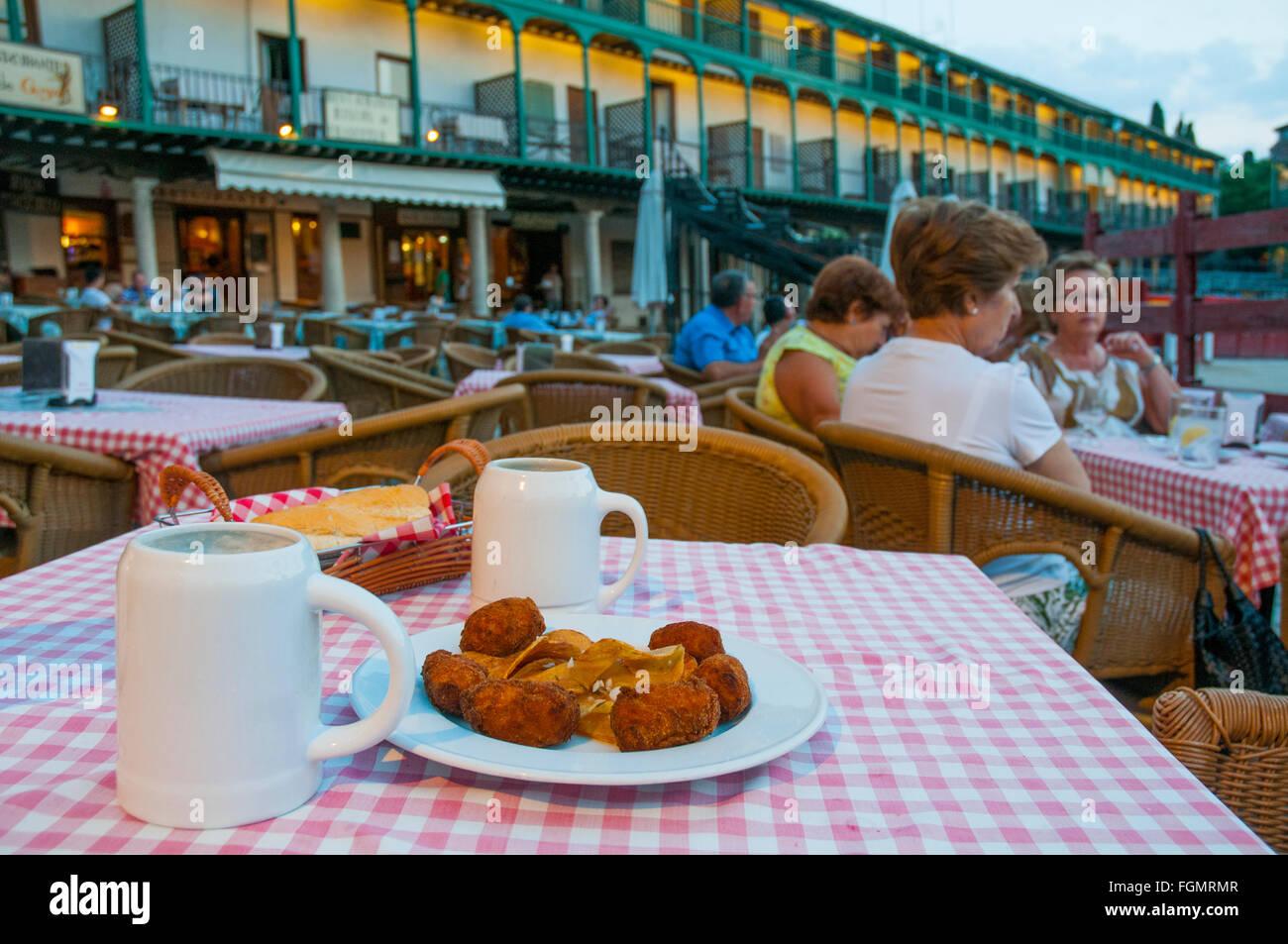 Tapa española: croquetas sirviendo y dos jarras de cerveza en una terraza al atardecer. Plaza principal, Chinchón, Imagen De Stock