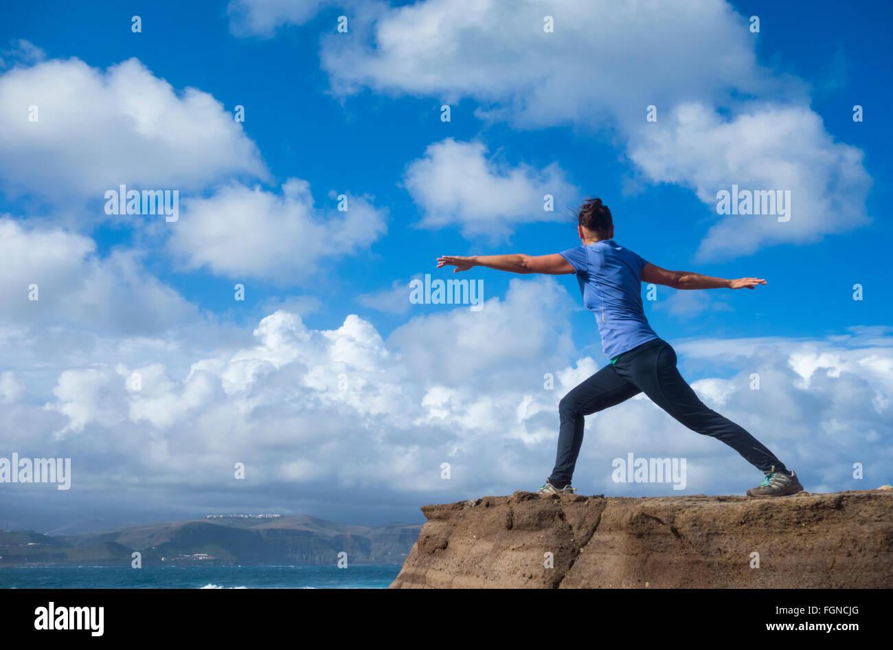 Emparejador de hembras maduras de calentamiento con Yoga ejercicios de estiramiento en roca con vistas al mar. Imagen De Stock