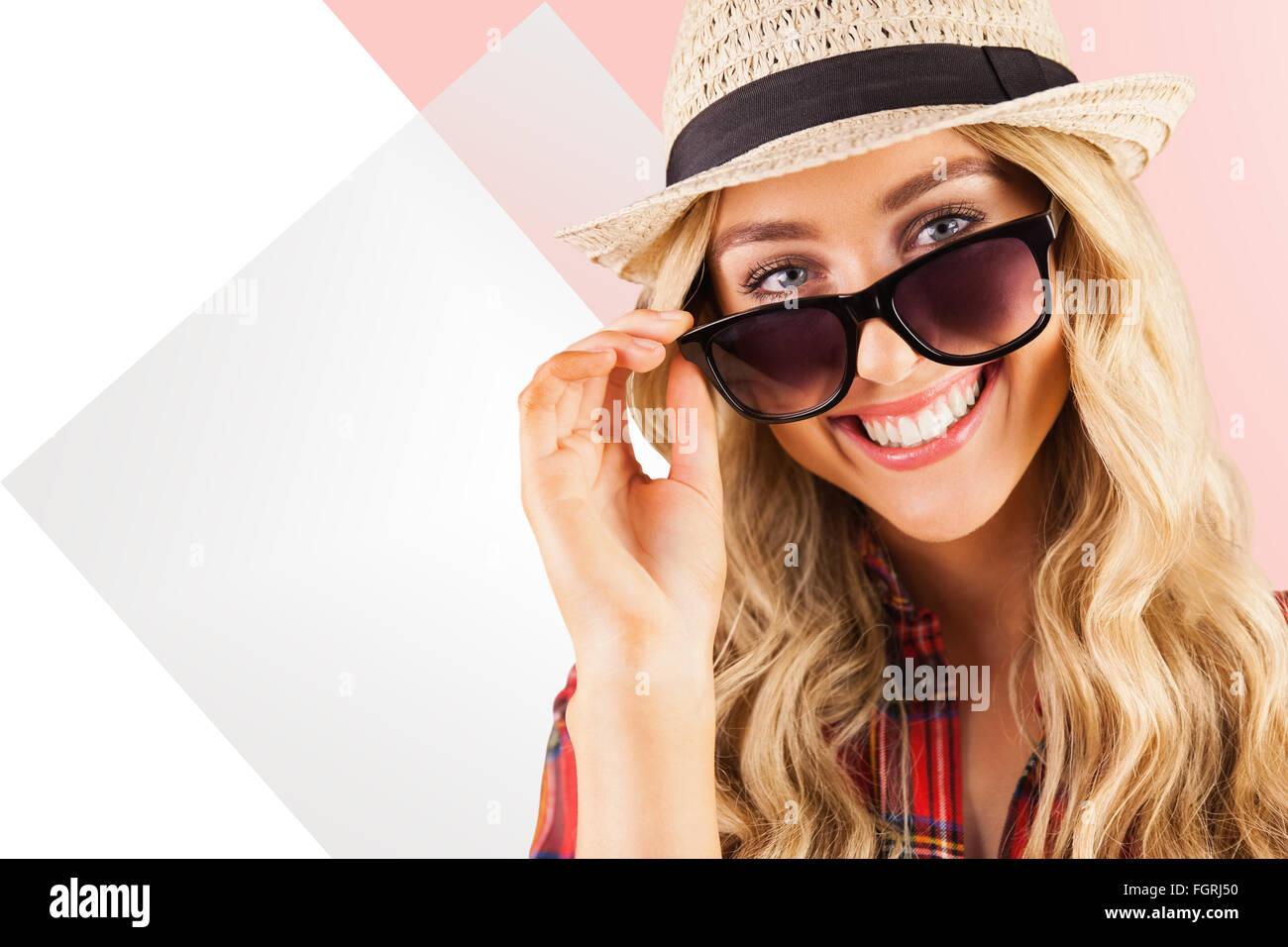 Imagen compuesta de hermosa rubia sonriente hipster posando con gafas de sol Foto de stock