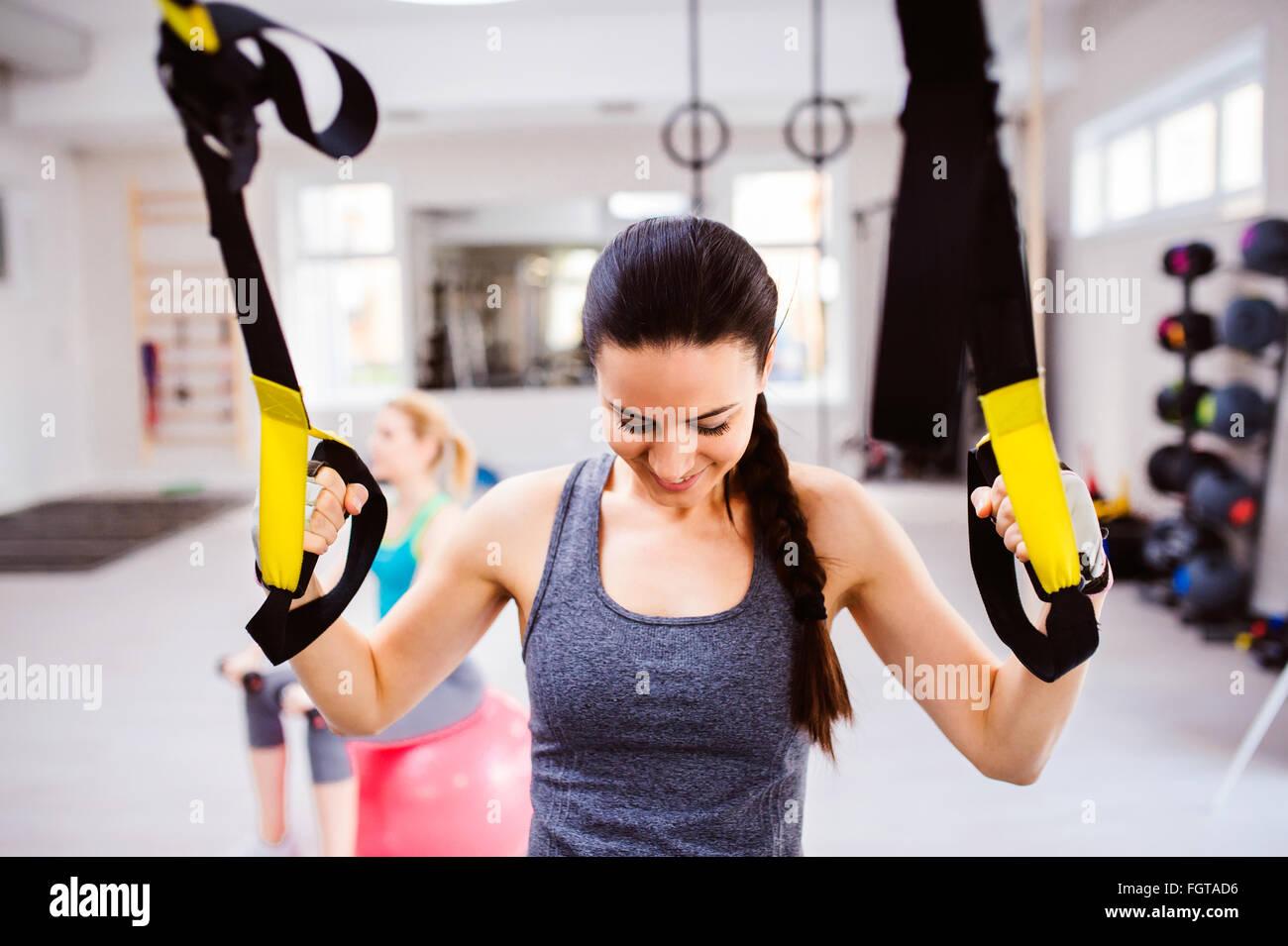 Mujer en el gimnasio entrenamiento brazos con tiras de fitness trx Foto de stock