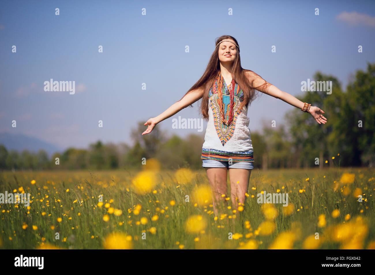 Libre y sonriente hippie en verano en el prado. Vintage efecto fotográfico. Imagen De Stock