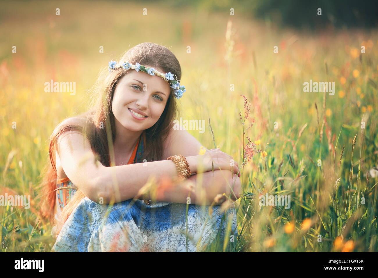Sonriente mujer romántica en campo de flores . Vestido de hippie y gitano Imagen De Stock