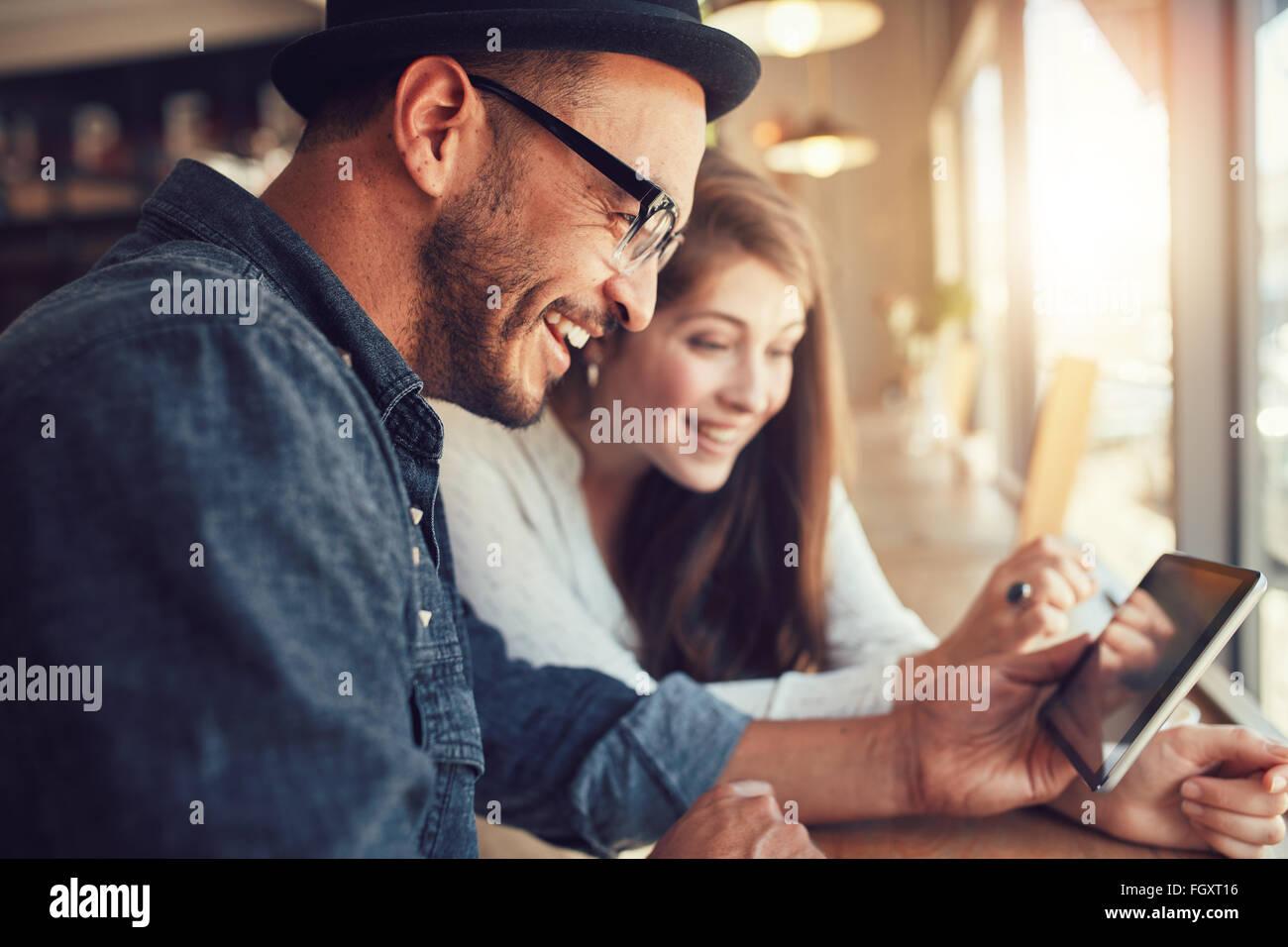 Close Up retrato de joven pareja feliz utilizando una tableta digital junto a una cafetería. Joven Hombre y Imagen De Stock