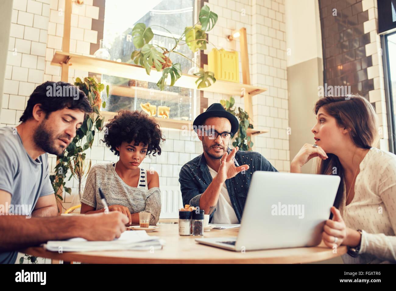 Retrato de negocio creativo equipo sentado en una cafetería con un portátil. Joven para debatir nuevas Imagen De Stock