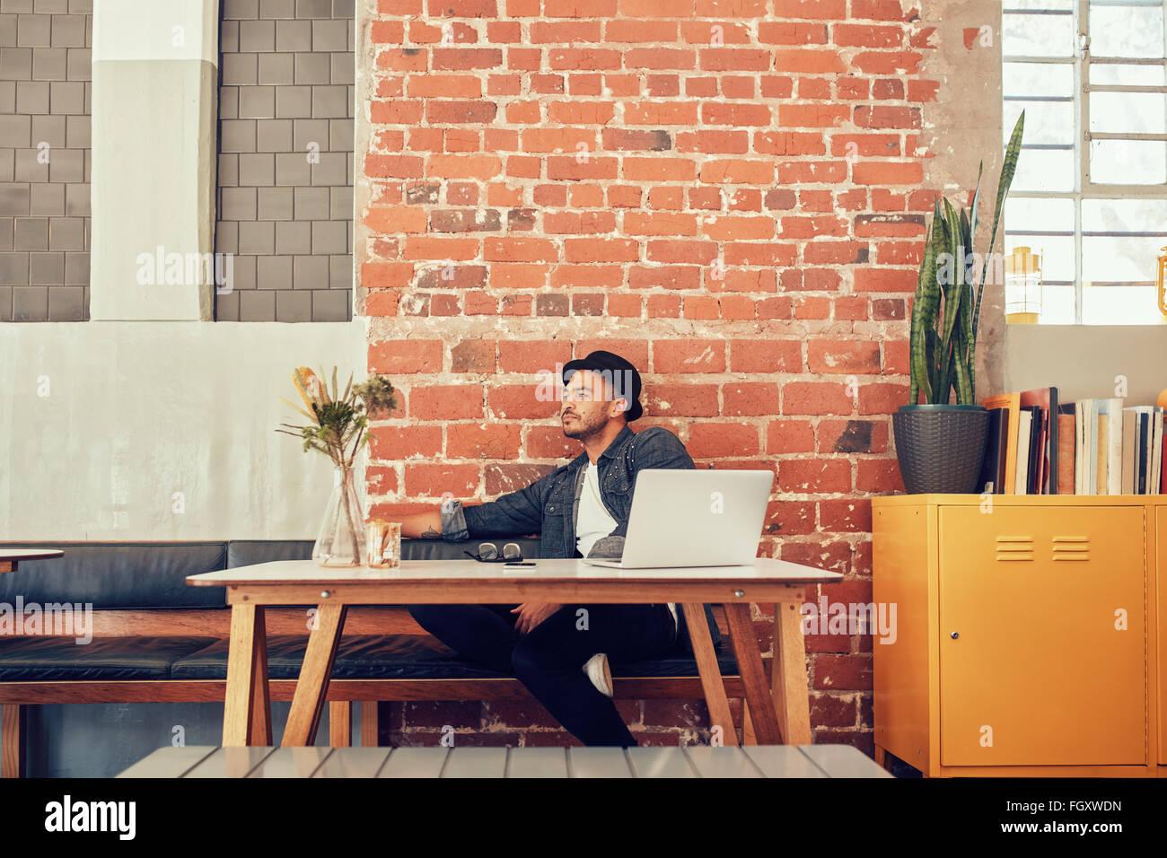 Retrato de joven sentada sola en un café con el ordenador portátil sobre la mesa. Hombre caucásico esperando que Foto de stock