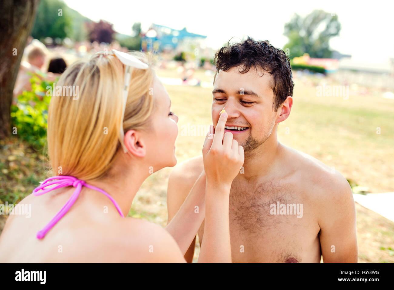 Mujer en bikini poner protector solar en la nariz del hombre Imagen De Stock