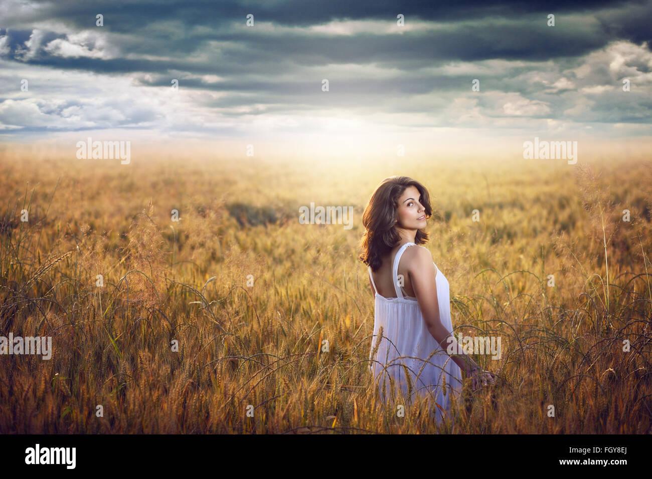 Bella mujer en un campo de maíz con dramáticas sky . Luz del atardecer Imagen De Stock