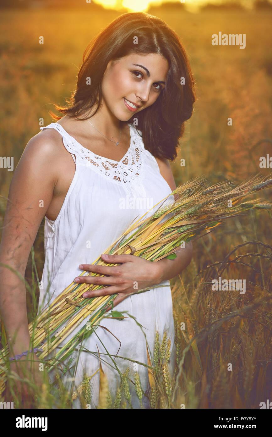 Bella mujer en un campo de cereal dorado rodeado por la luz del atardecer de verano Imagen De Stock