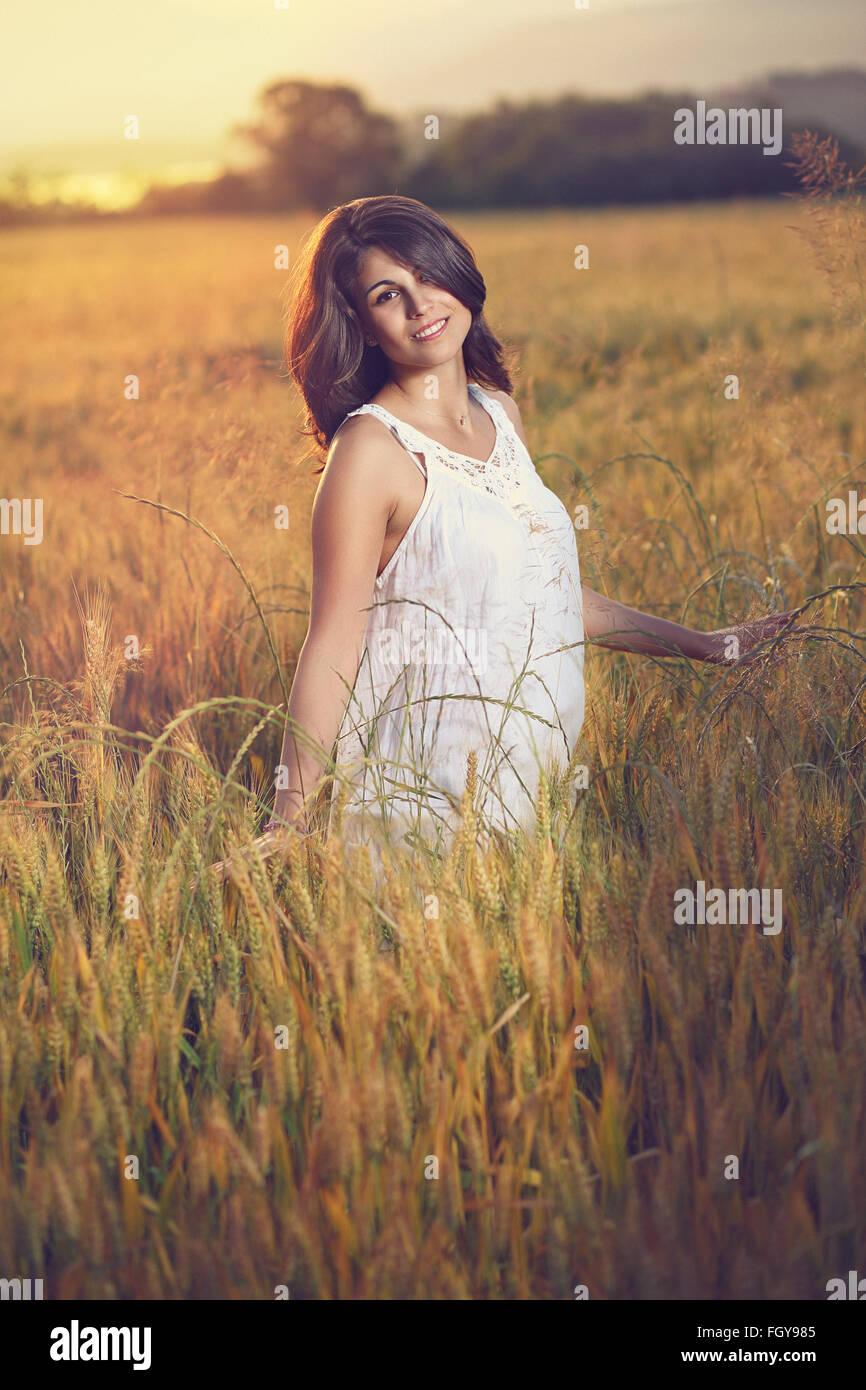 Bella mujer plantea en un campo al atardecer. Temporada de verano retrato Foto de stock