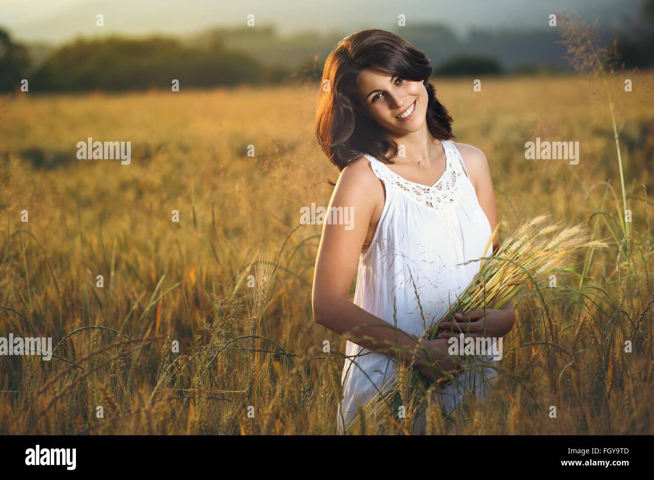 Hermosa mujer sonriente en un campo dorado al atardecer. Temporada de verano retrato Imagen De Stock