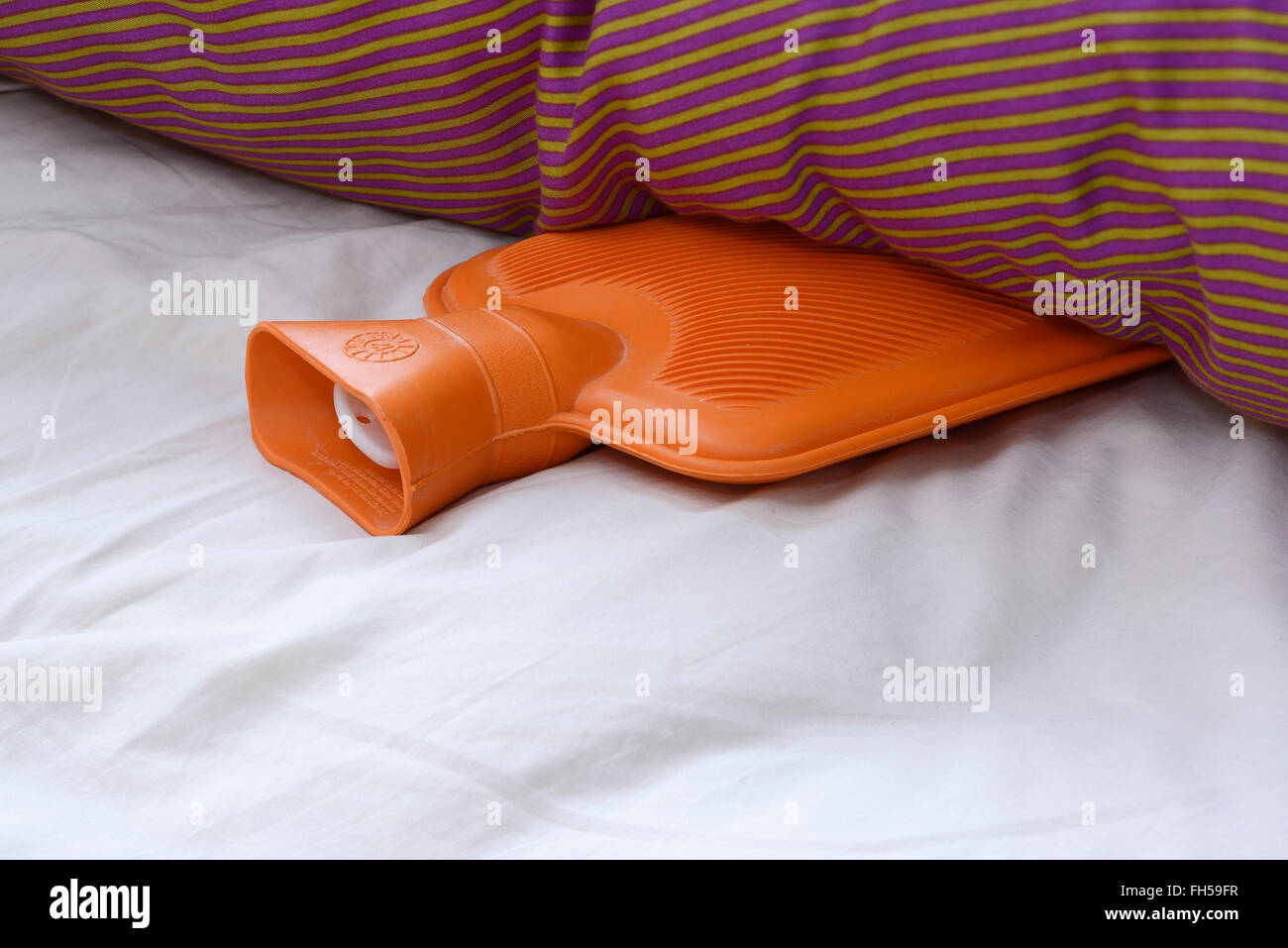 Una botella de agua caliente de caucho naranja acostado en una cama Imagen De Stock