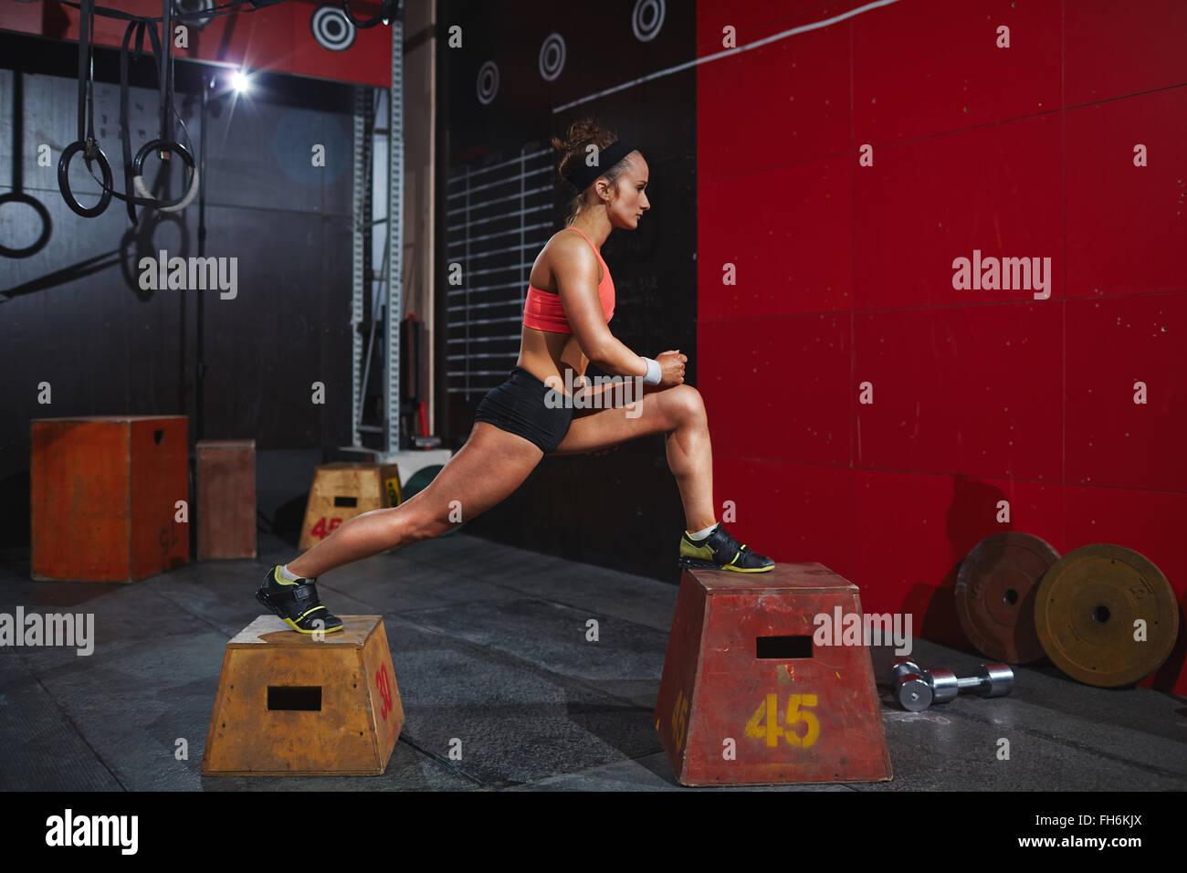 Mujer joven en active-wear formación sobre cuadros de saltar en el gimnasio Imagen De Stock