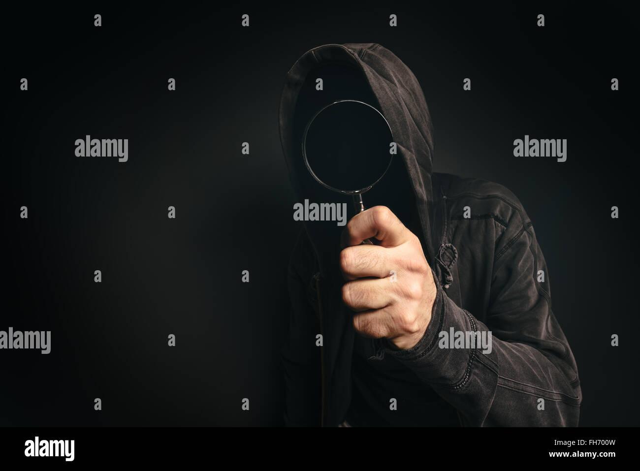 Spyware, software informático encapuchado spooky persona con lupa mirar usted Imagen De Stock