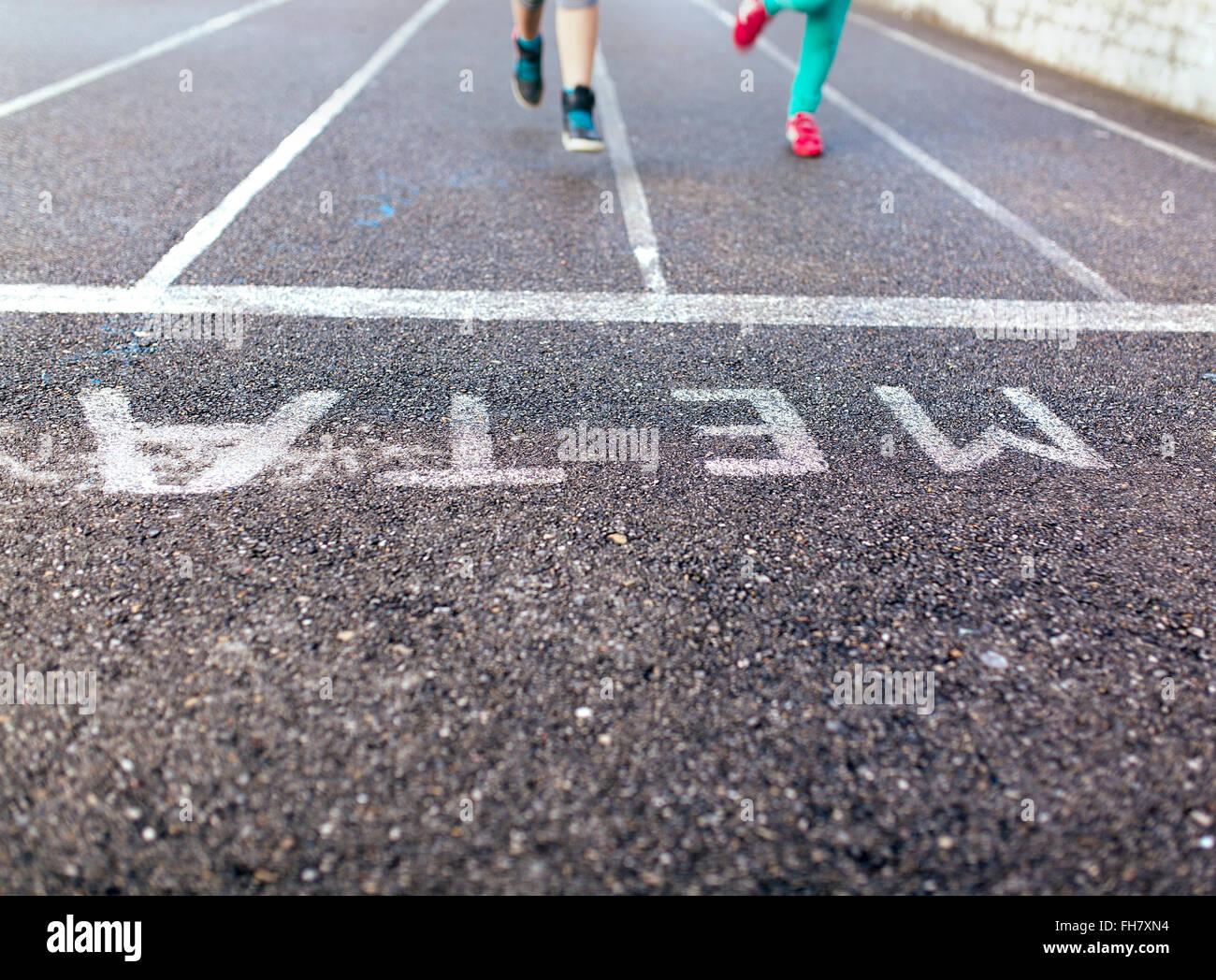 Las piernas de dos niñas en asfalto Imagen De Stock
