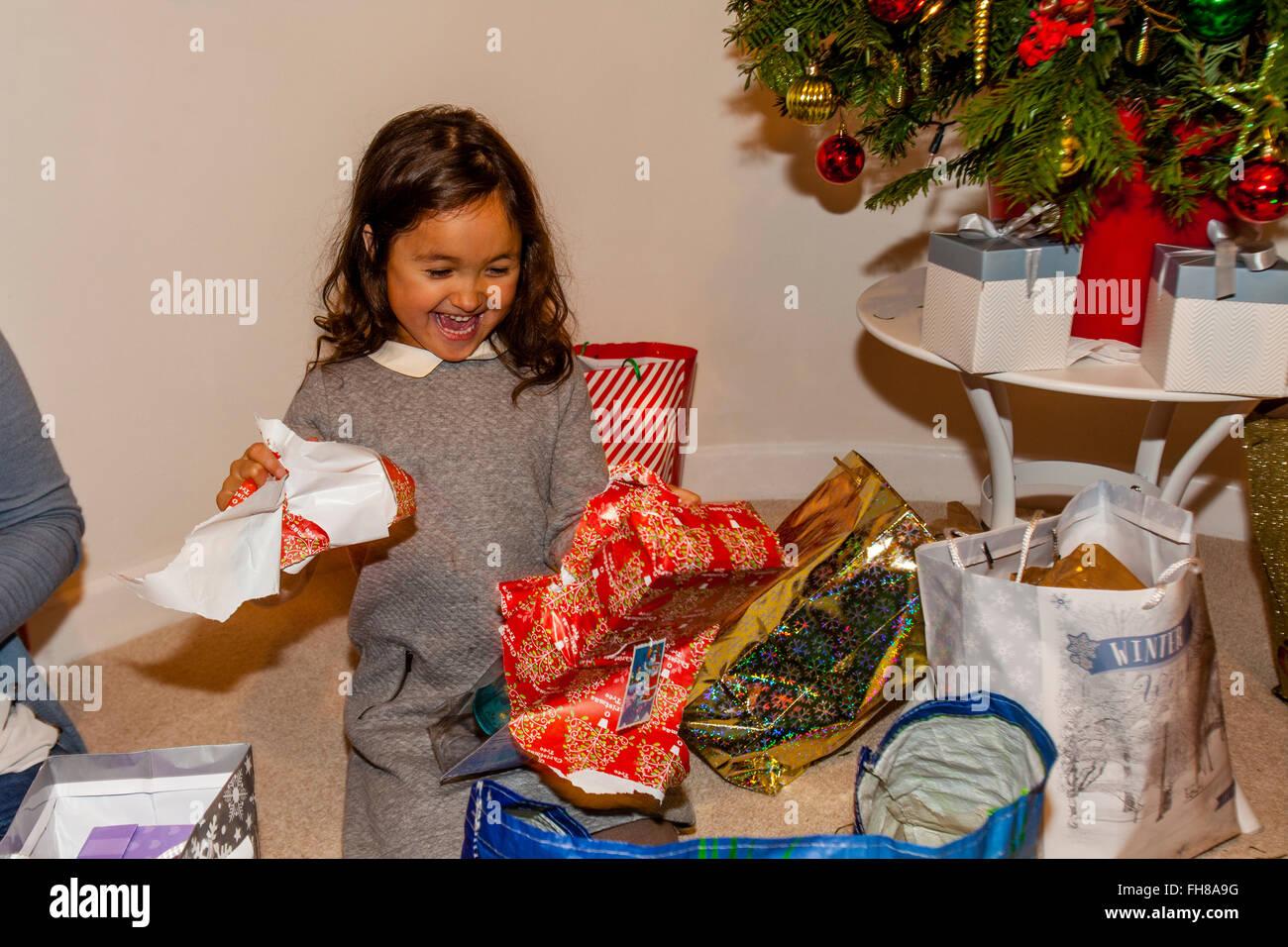 Una raza mixta niño abriendo sus regalos de Navidad el día de Navidad, Brighton, Sussex, Reino Unido Imagen De Stock