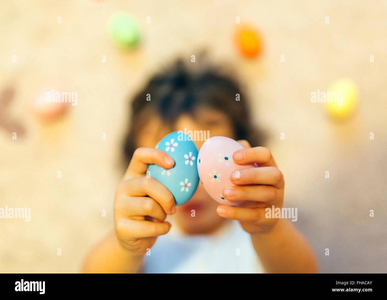 Chica manos sosteniendo dos huevos de Pascua pintados Imagen De Stock