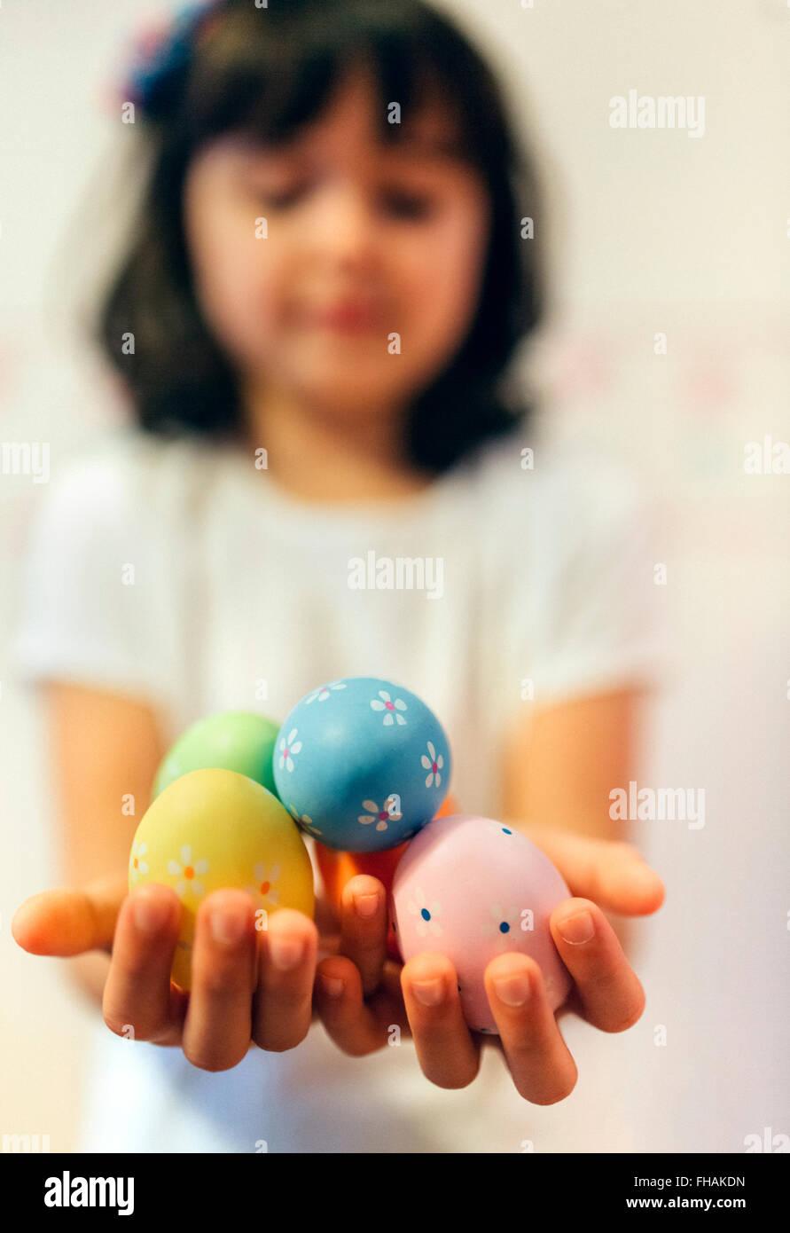 Chica manos agarrando los huevos de Pascua pintados Imagen De Stock