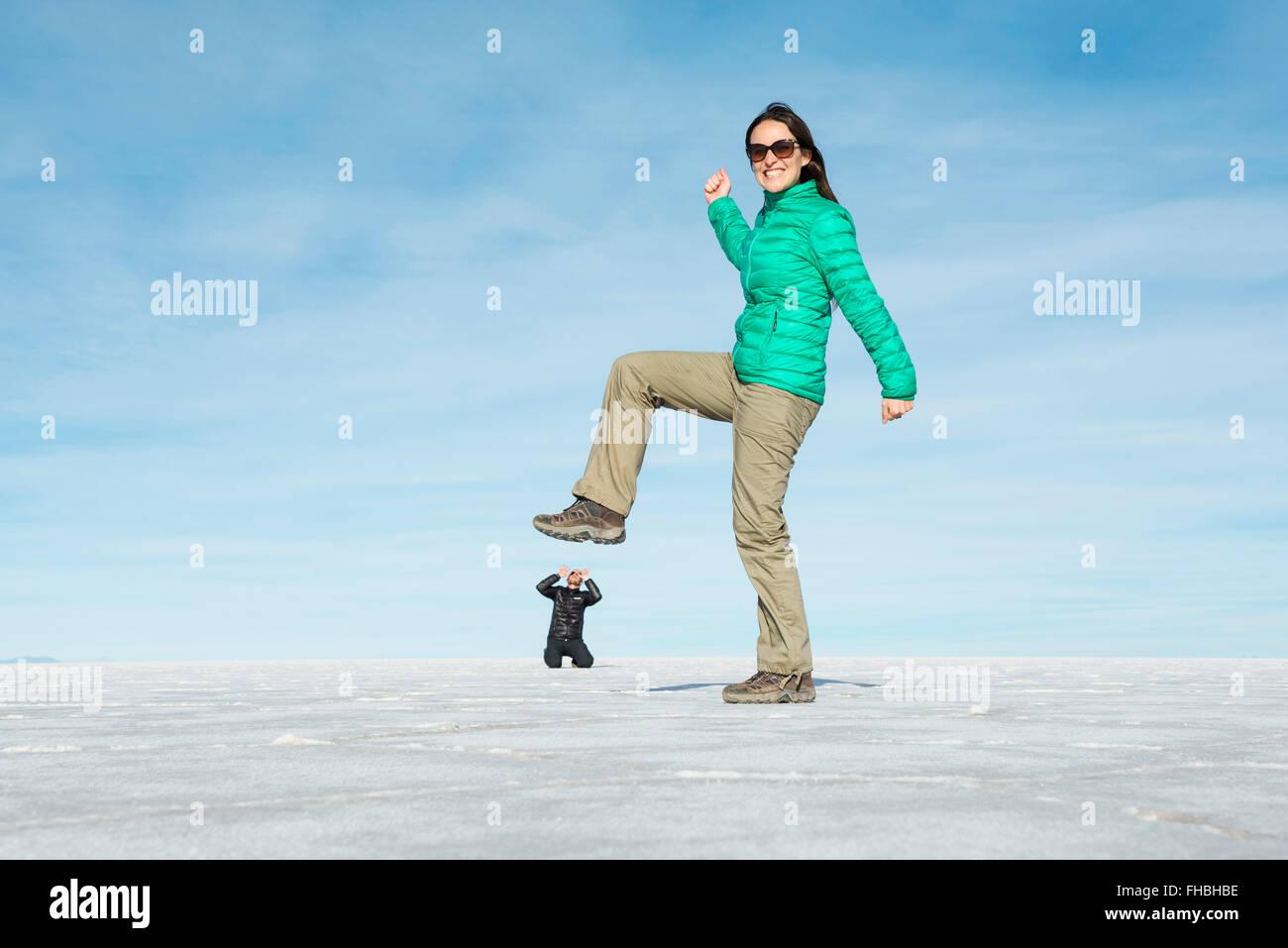 Bolivia, el Salar de Uyuni, mujer pateando pequeño hombre, ilusión visual Imagen De Stock