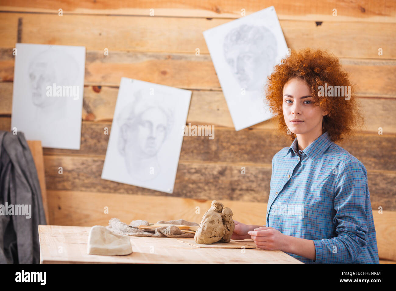 Bella pelirroja mujer potter sentado y el trabajo con la arcilla en el taller Imagen De Stock