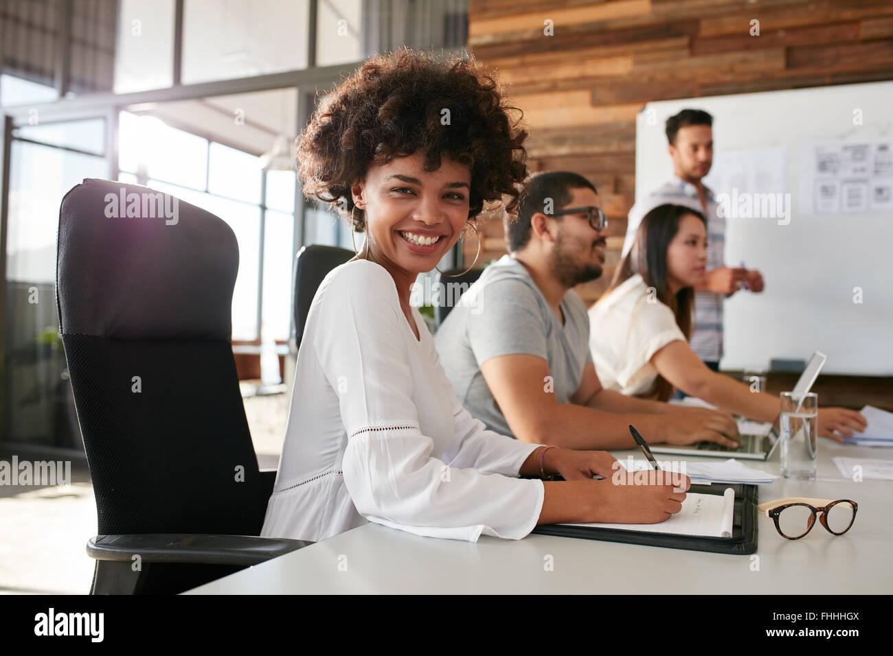Retrato de feliz joven africana sentado en la presentación de un negocio con sus colegas en la sala de juntas. Imagen De Stock