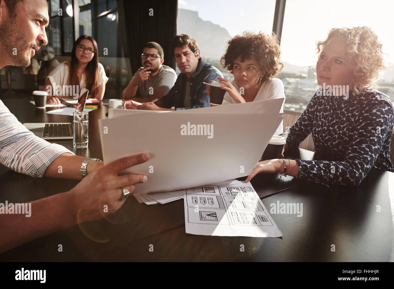 Closeup foto de equipo de los jóvenes va más papeleo. Las personas creativas reunión en mesa de restaurante. Imagen De Stock