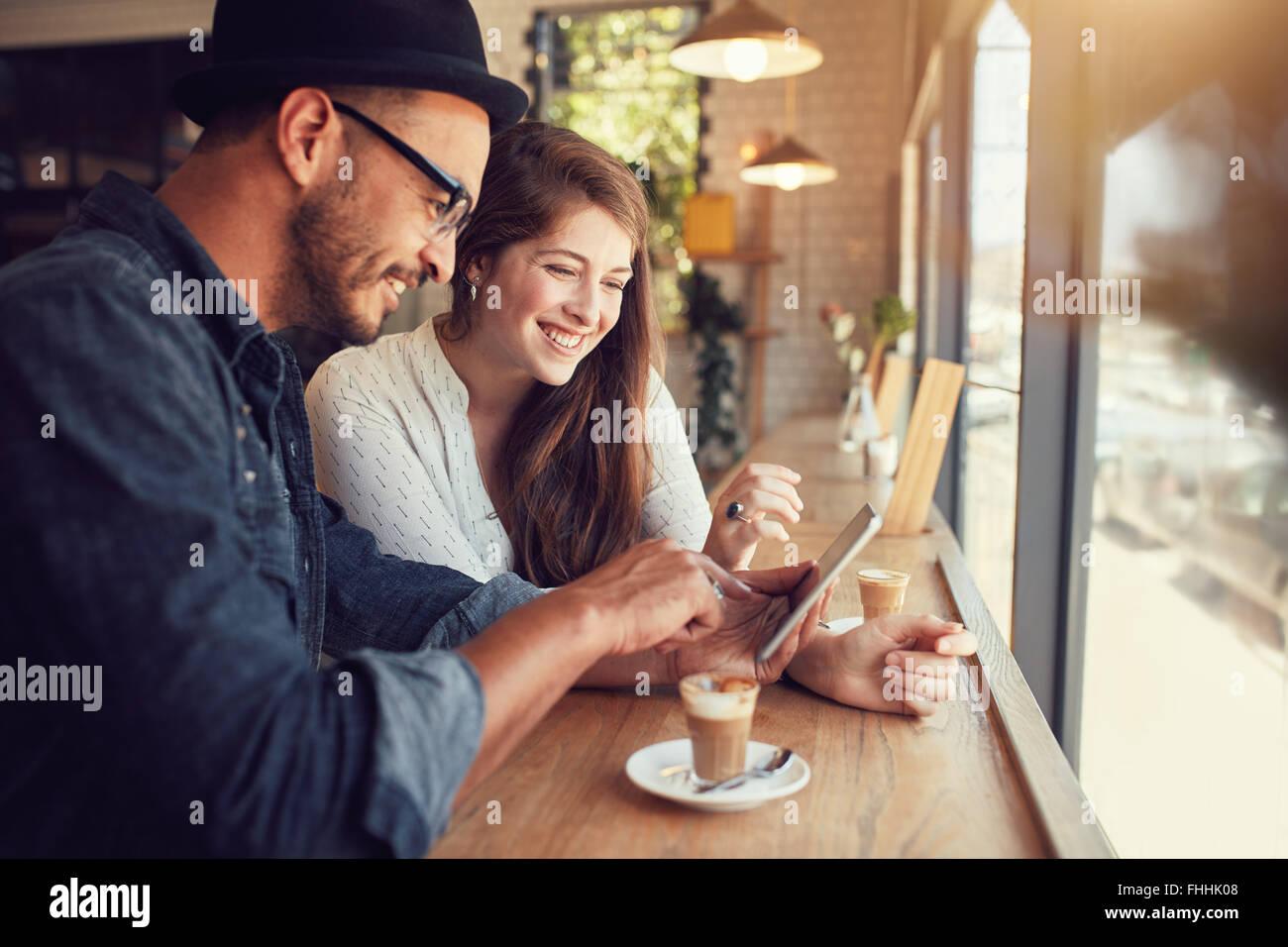 Feliz pareja en una cafetería navegando por internet en tableta digital. El hombre y la mujer joven en un restaurante Imagen De Stock