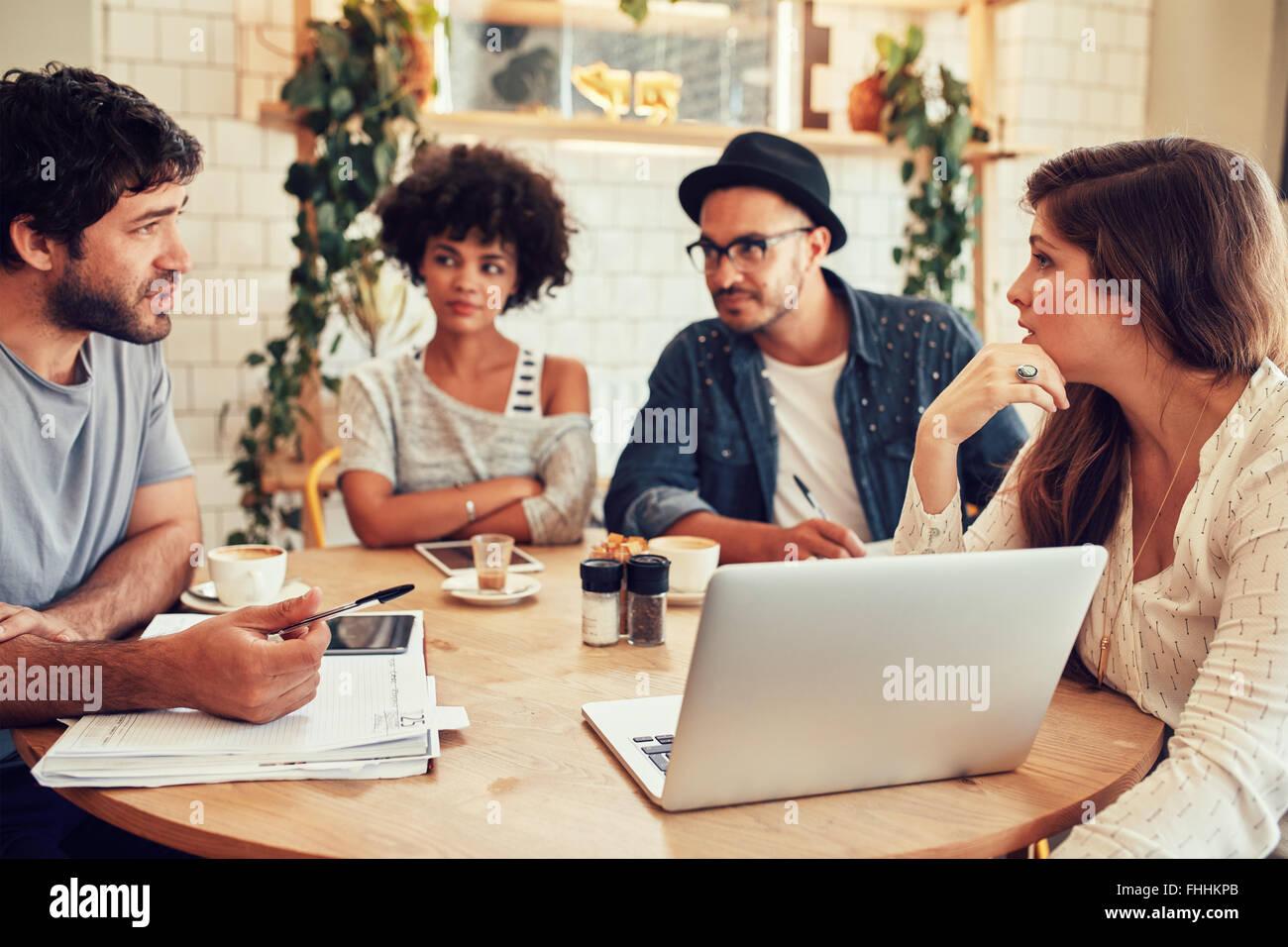 Retrato de jóvenes sentados en la cafetería con un portátil. Reunión del equipo creativo en Imagen De Stock