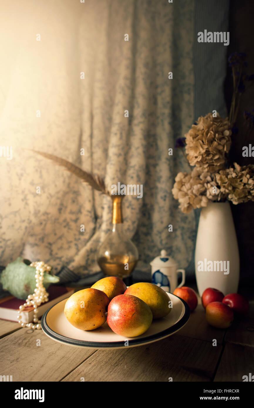 Bodegón con frutas, jarrón con flores,botella de cristal y plumas Imagen De Stock