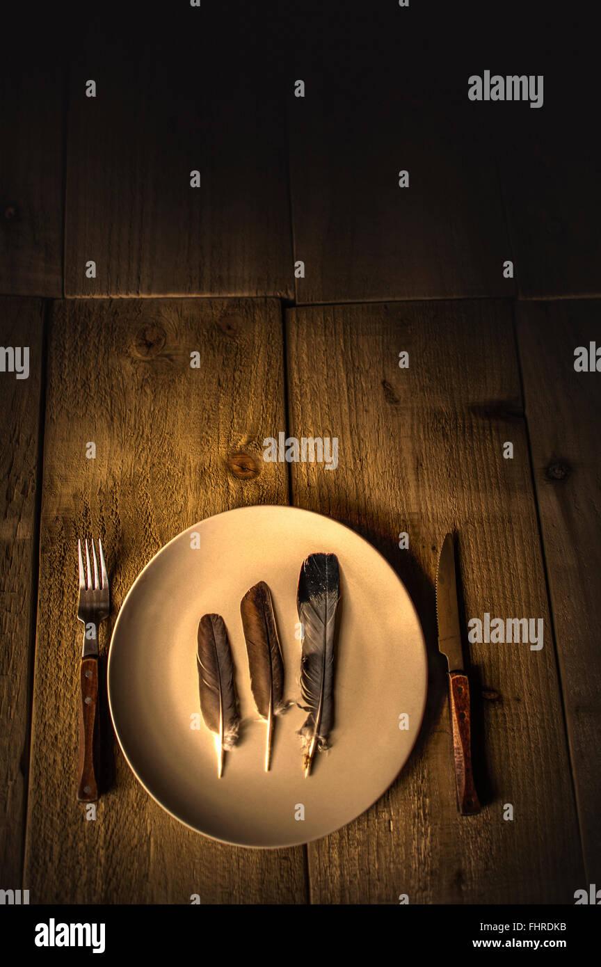 Bodegón con plumas en un plato y tenedor y cuchillo sobre mesa de madera Imagen De Stock