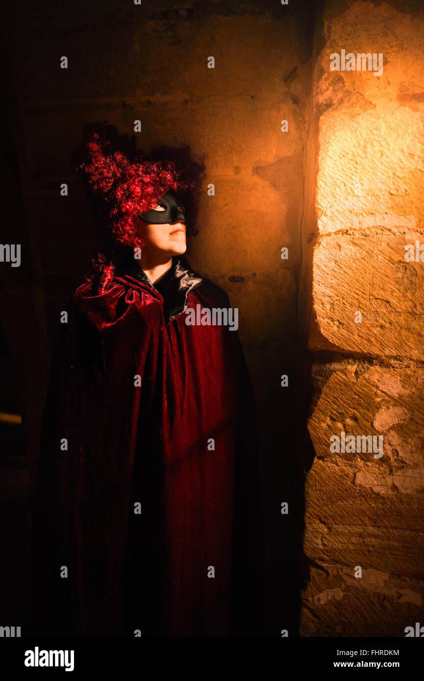 Figura femenina vestidos de rojo peluca de pie en el castillo por la ventana Imagen De Stock