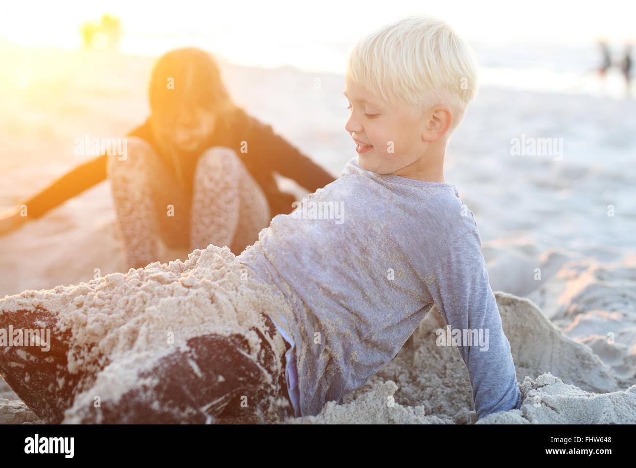 Niños en la playa jugando en la arena. Felices los niños y niñas jugando en una playa de arena Imagen De Stock