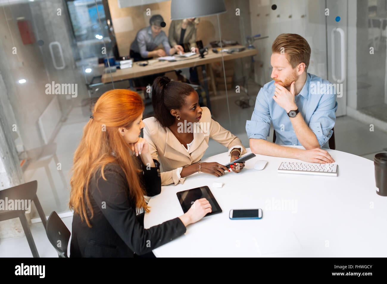 Los empresarios reunidos en mesa redonda y la reflexión Imagen De Stock