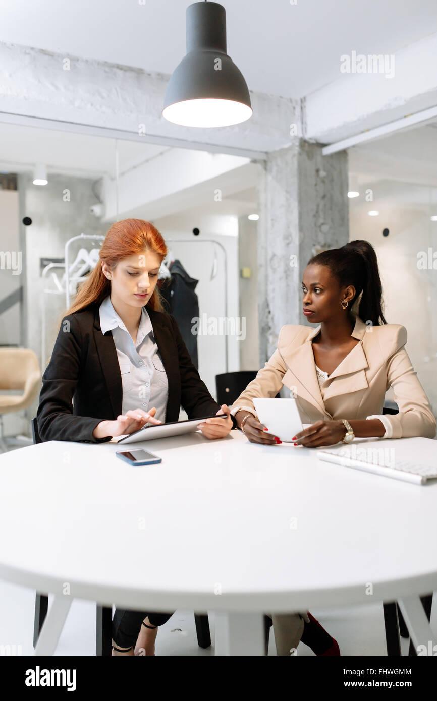 Dos atractivas mujeres empresarias mediante la tecnología mientras está sentado en la oficina inmaculada Foto de stock