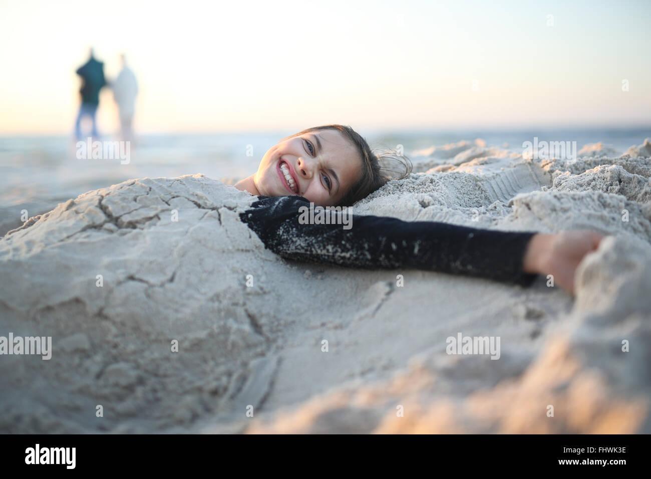 Playa, alegría y diversión. Riendo, niña alegre tumbado en una playa de arena Imagen De Stock