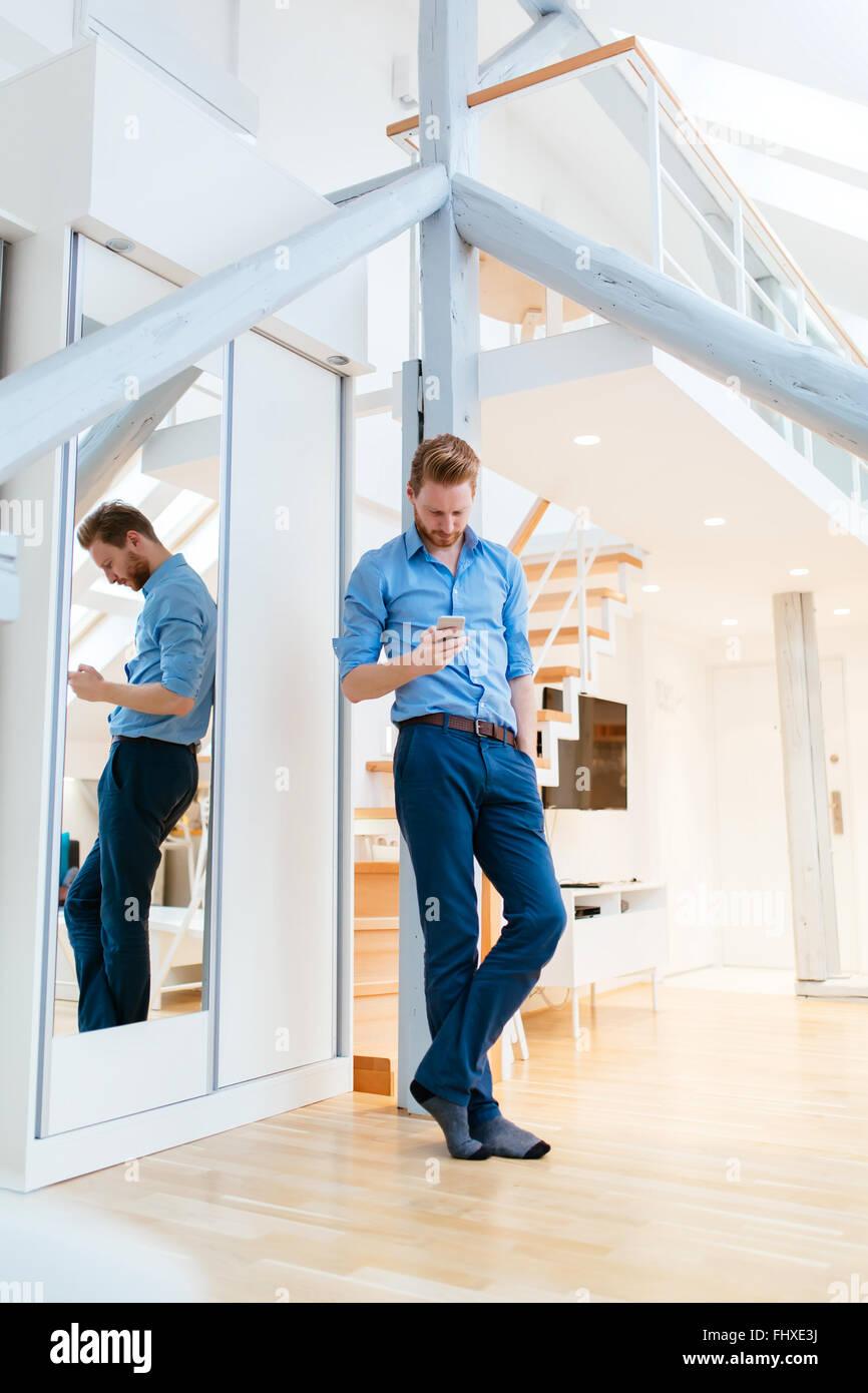 Hombre utilizando el teléfono en el hermoso apartamento moderno vistiendo camisetas Imagen De Stock