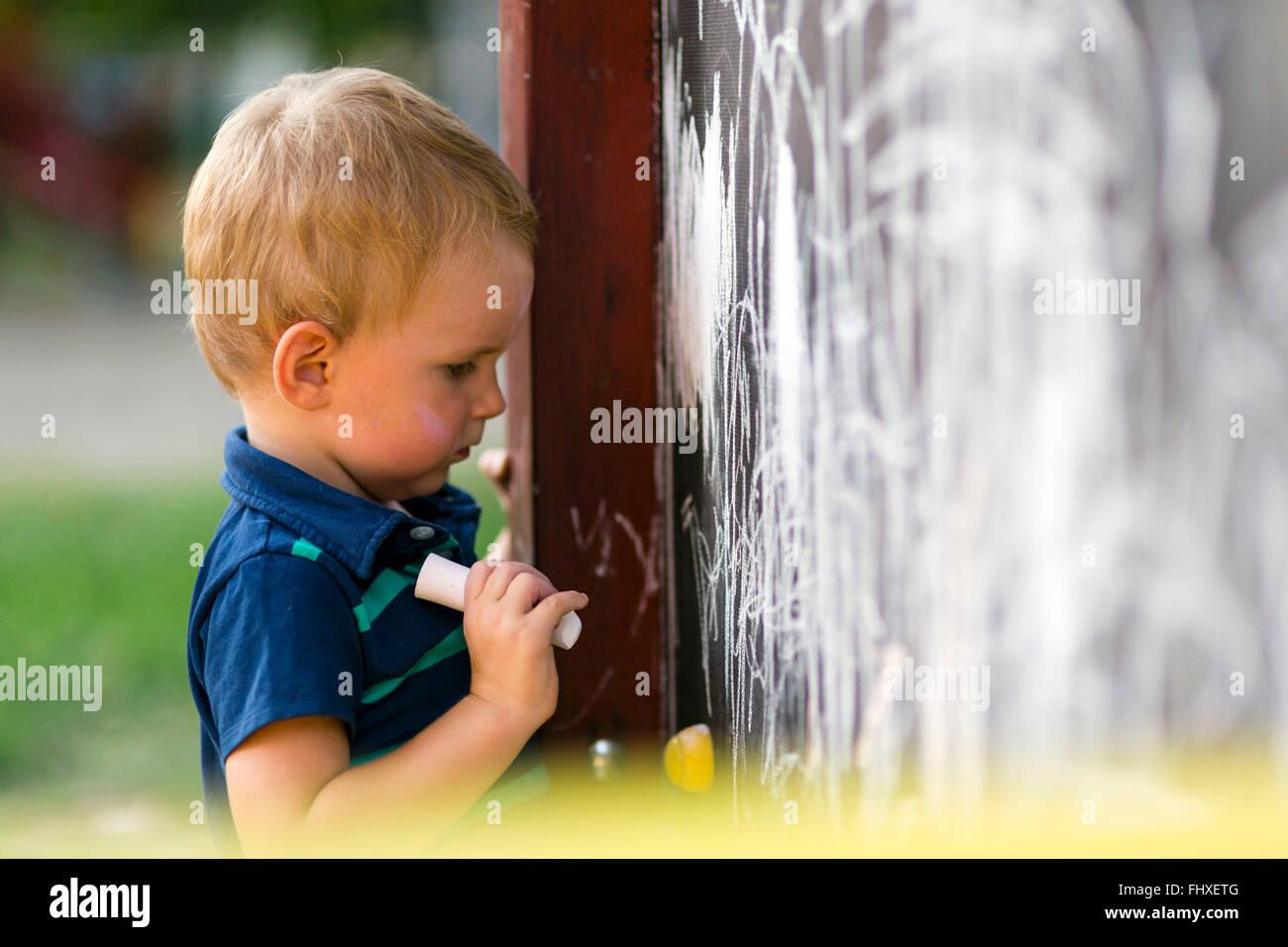 Niño lindo creativo de dibujo con tiza en un tablero de dibujo al aire libre Imagen De Stock