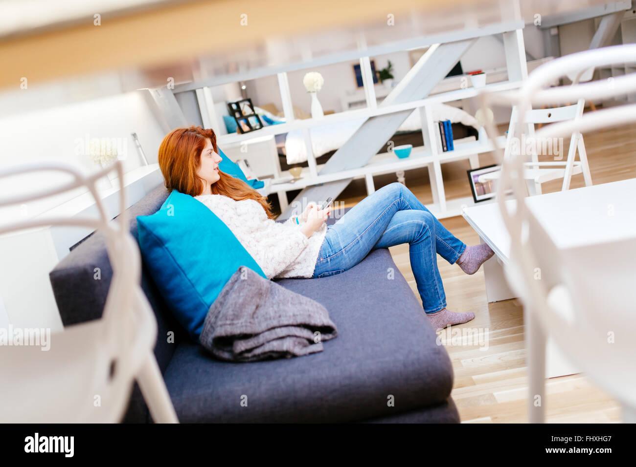 Hermosa mujer de pelo rojo utilizando el teléfono mientras está sentado en el sofá Foto de stock