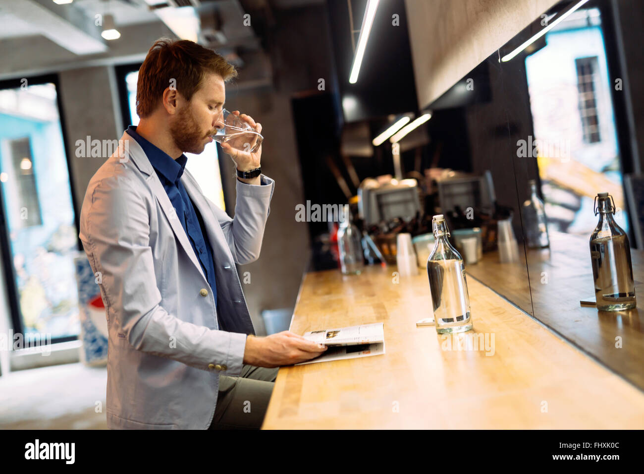 Empresario de agua potable y la lectura matutino Imagen De Stock