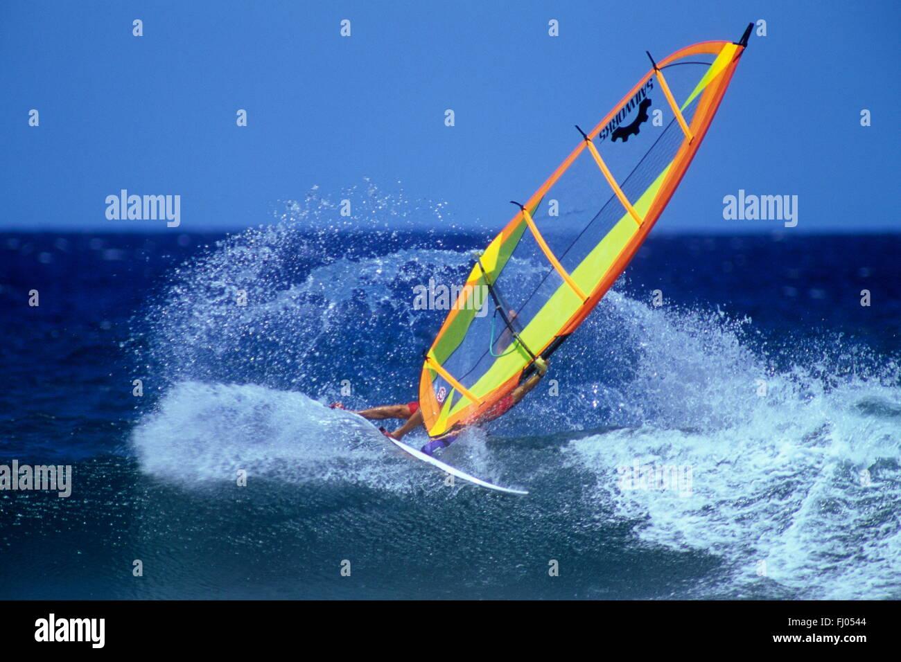 Casi patinando sobre la onda realiza una tabla de windsurf con vela de color amarillo brillante en el Pacífico Imagen De Stock