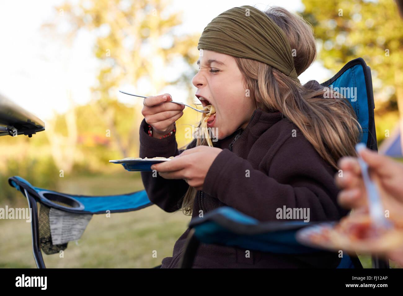 Muchacha comiendo espaguetis en el camping Foto de stock