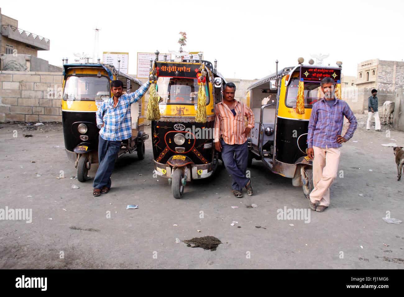 Los conductores de rickshaw stand by su vehículo en Jaisalmer, India Imagen De Stock